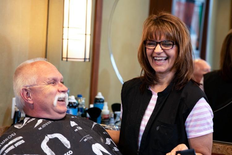 Staff member getting hair cut