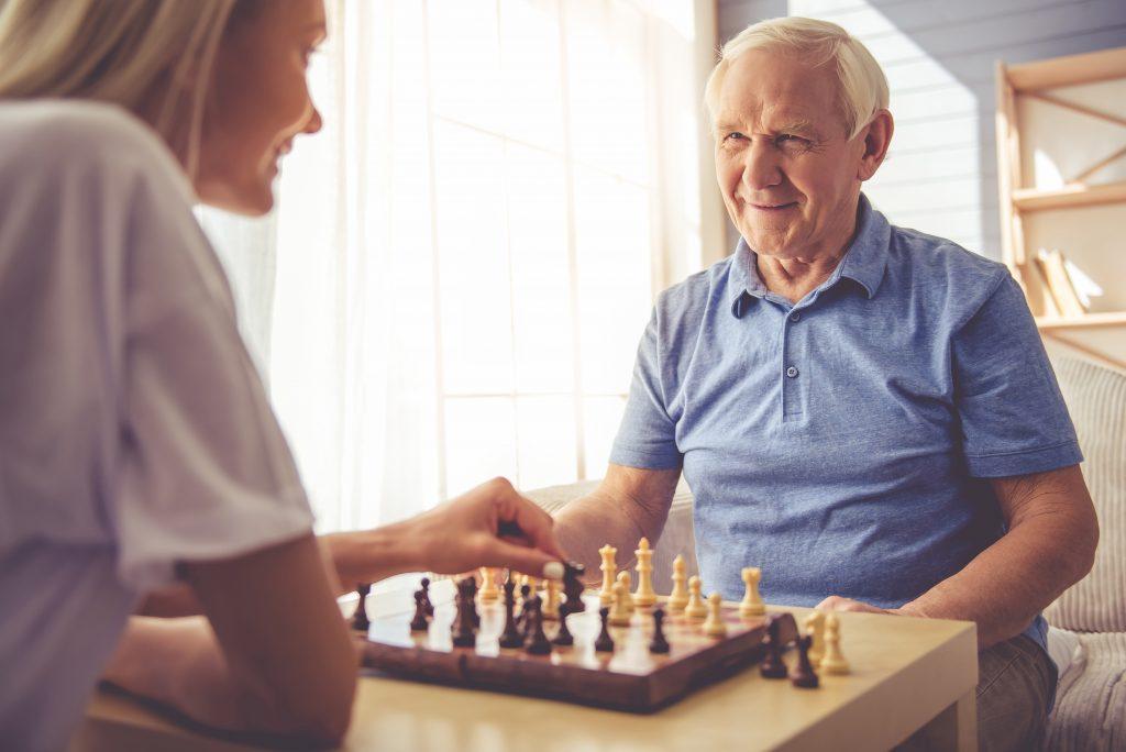 Senior Man playing chess with volunteer
