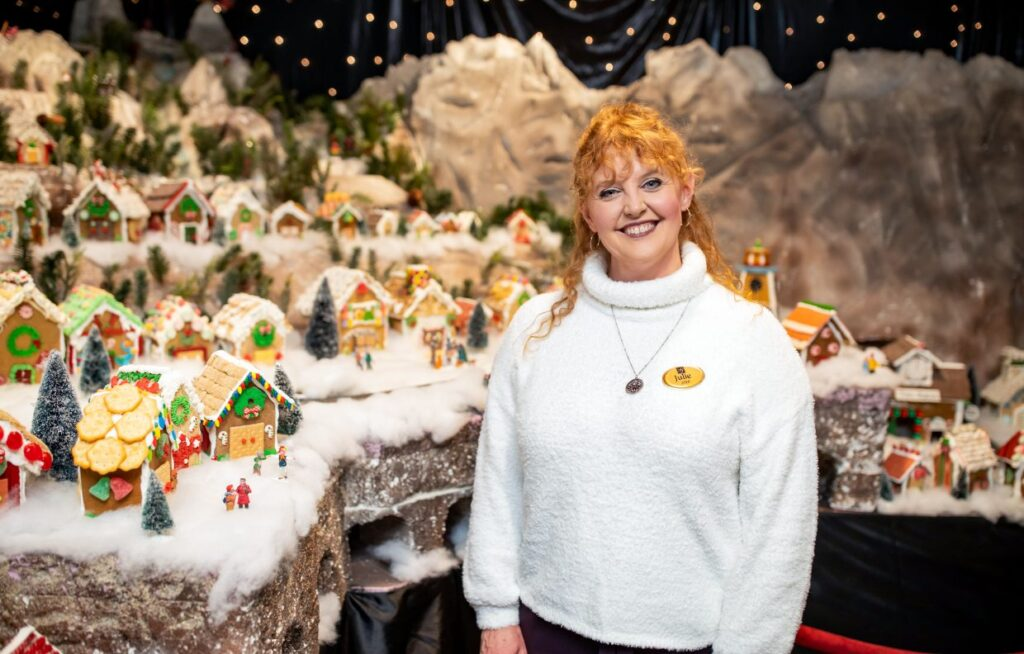 Julie posing with Gingerbread Village