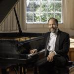 Fredrick Moyer sitting at his piano smiling