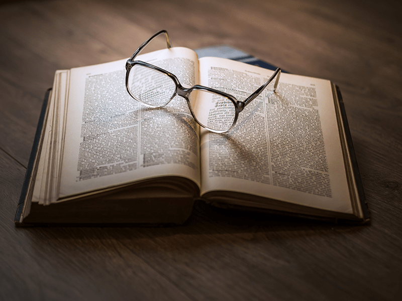 Opened novel with a pair of glasses resting on top