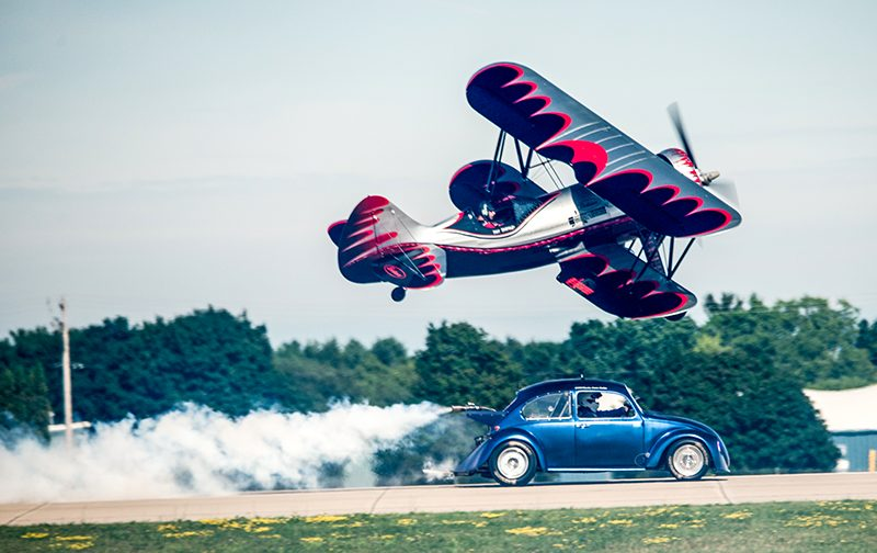 bi-plane flying over a volkswagon