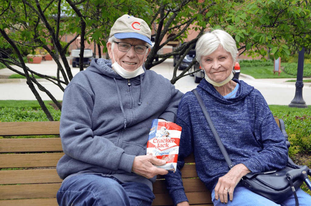 Senior couple eating some Cracker Jacks while sitting on a bench.