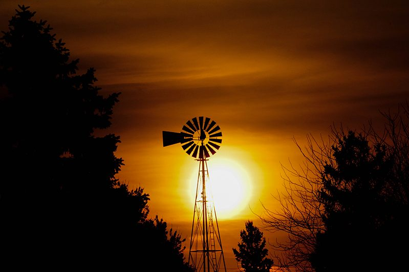 Wind mill agains an orange sunset