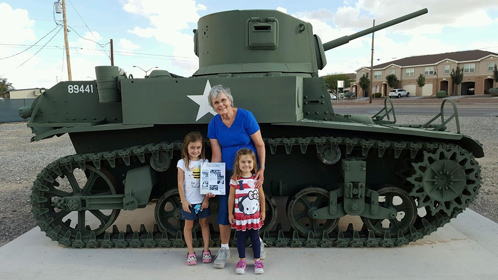 Joyce and her grandchildren in front of an army tank