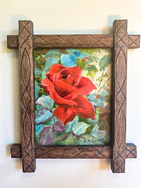 Rose painting in a wood carved frame.