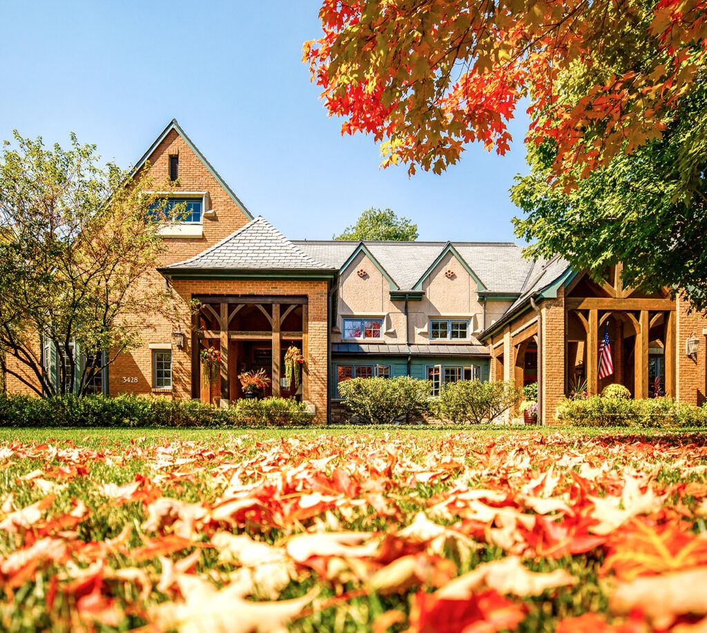 A Garlands Villa with fall leaves on the ground and tree changing colors