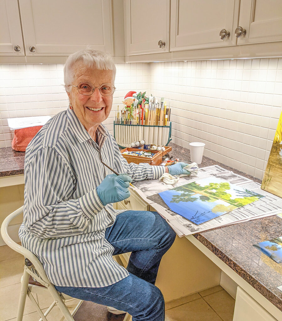 Marlene Peterson painting in her kitchen
