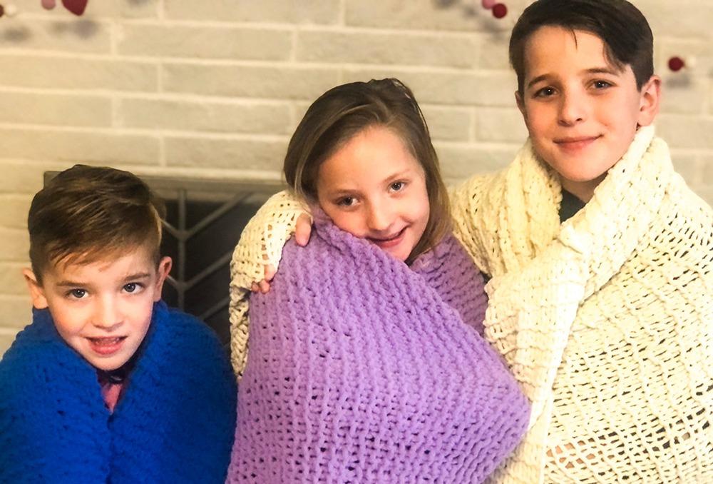 Grandchildren with knitted blankets
